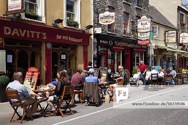 Patrons sitting on outdoor patios outside restaurants; Kenmare,  County Kerry,  Ireland
