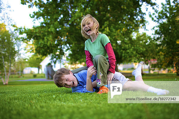'A boy and girl wrestling on the grass; Picton  Ontario  Canada'