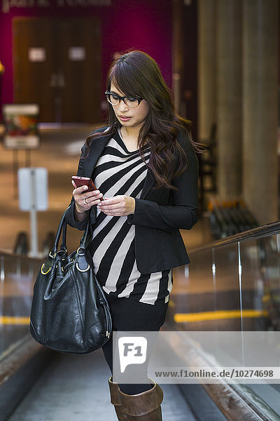 'Young woman shopping at a mall and checking her cell phone for messages; St. Albert  Alberta  Canada'