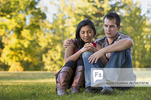'Mixed race couple praying together in a park in autumn; St. Albert  Alberta  Canada'