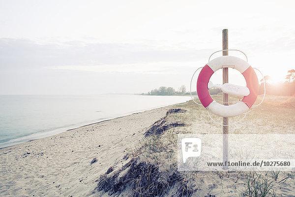 Rettungsring an der Stange am Strand an einem sonnigen Tag