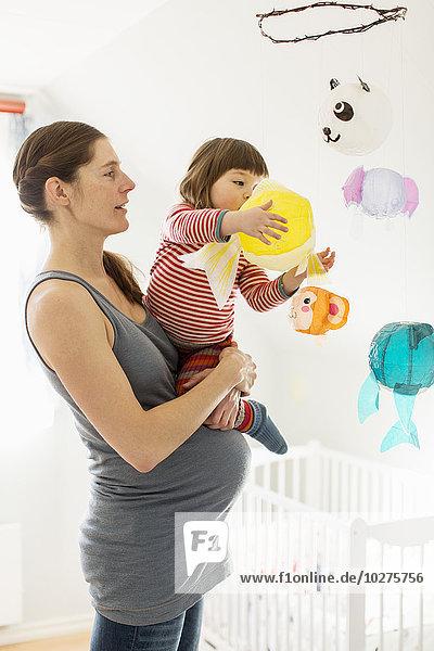 Schwangere Frau  die ein Mädchen trägt  das mit Spielzeug im Babyzimmer spielt. Schwangere Frau, die ein Mädchen trägt, das mit Spielzeug im Babyzimmer spielt.