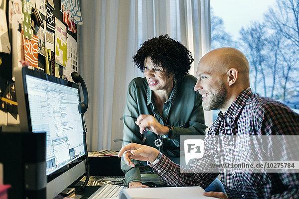 Glückliche Geschäftsleute  die am Computer im Büro arbeiten