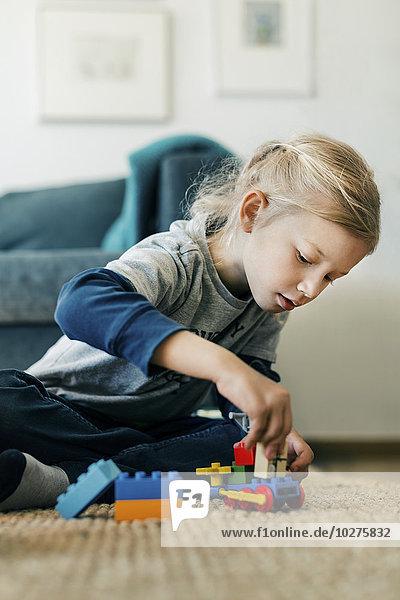 Mädchen machen Spielzeugauto mit Blöcken beim Sitzen auf dem Boden zu Hause