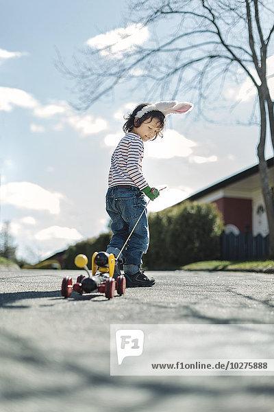 Volle Länge des Jungen  der Spielzeugauto auf dem Gehweg am Hof zieht.