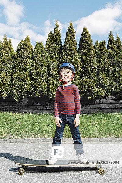 Porträt eines glücklichen Jungen  der auf einem Skateboard gegen Bäume steht.