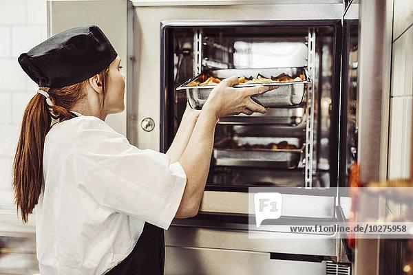Seitenansicht der Köchin beim Backen in der Großküche