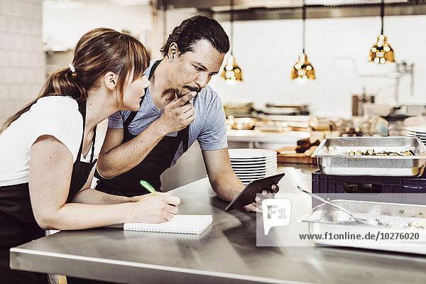Köche und Köchinnen mit digitalen Tabletts beim Schreiben von Rezepten an der Großküchentheke