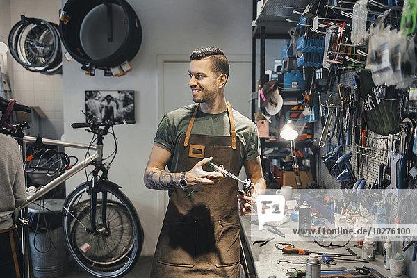 Lächelnder Mechaniker schaut Kollegen bei der Pedalreparatur in der Werkstatt an