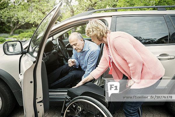 Frau unterstützt behinderten Mann beim Aussteigen aus dem Auto