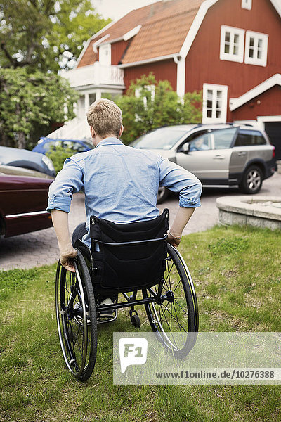 Rückansicht des Rollstuhlfahrers auf dem Hof