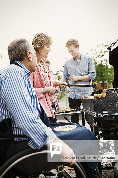 Großeltern mit Brüdern beim Grillen auf dem Hof