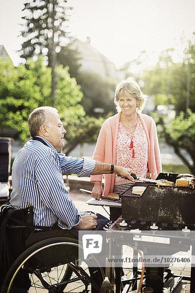 Glückliches reifes Paar beim Grillen auf dem Hof