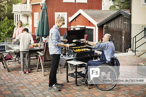 Disabled man serving barbecued food to son at yard