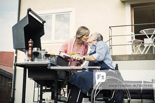 Behinderter Mann im Rollstuhl küssende Frau beim Grillen auf dem Hof