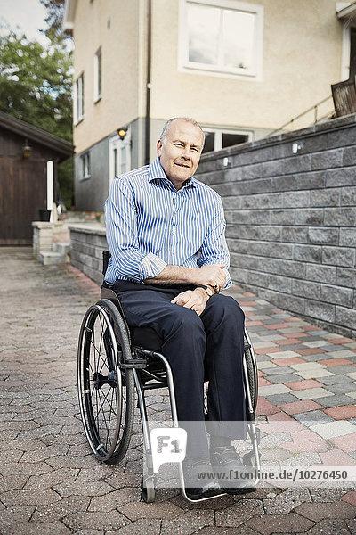 Porträt eines selbstbewussten Mannes im Rollstuhl auf der Straße