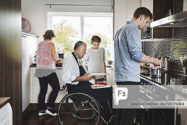 Eltern und Kinder bei der gemeinsamen Zubereitung von Speisen in der Küche