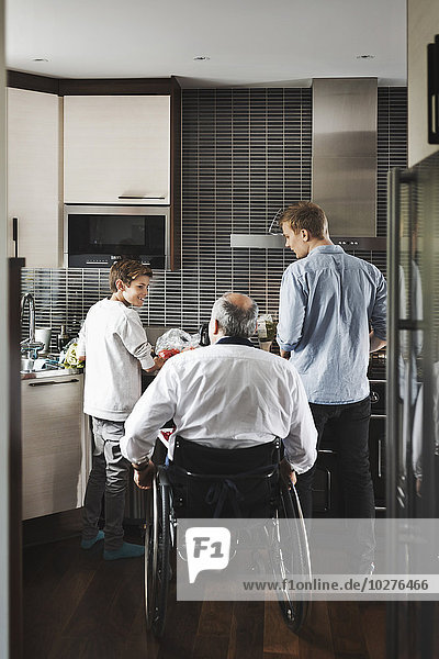 Rückansicht des behinderten Vaters im Rollstuhl mit Söhnen in der Küche