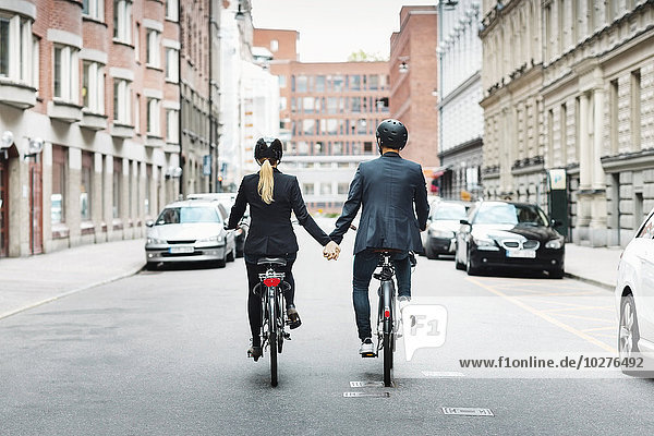 Rear view of business people holding hands while riding bicycles on street