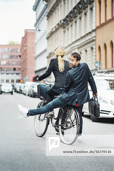 Rear view portrait of happy businessman sitting on back seat while female colleague riding bicycle