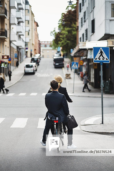 Rear view of business people riding bicycle on city street