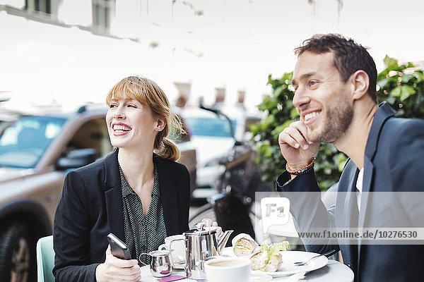 Fröhliche Geschäftsreisende schauen weg  während sie auf dem Bürgersteig sitzen.