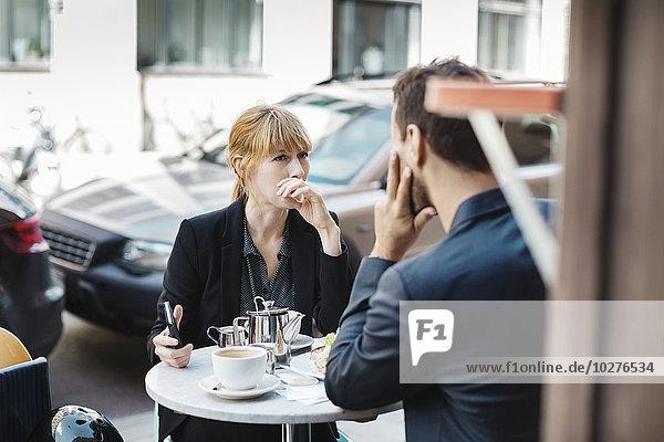 Pendlerinnen und Pendler sitzen im Straßencafé