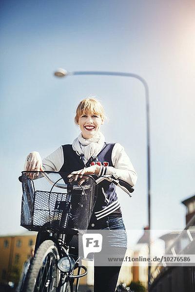 Porträt einer glücklichen Geschäftsfrau mit dem Fahrrad am Himmel