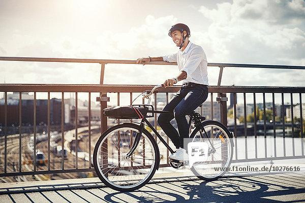 Glücklicher Geschäftsmann mit Fahrrad auf der Brücke in der Stadt