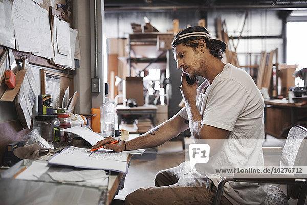 Seitenansicht des Schreiners mit dem Handy beim Lesen von Dokumenten in der Werkstatt