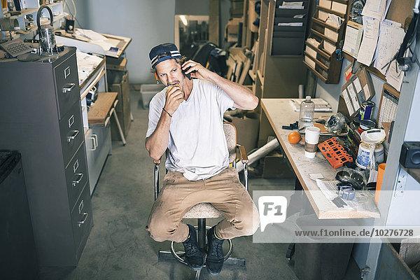 Hochwinkelansicht des Schreiners mit dem Handy im Sitzen in der Werkstatt