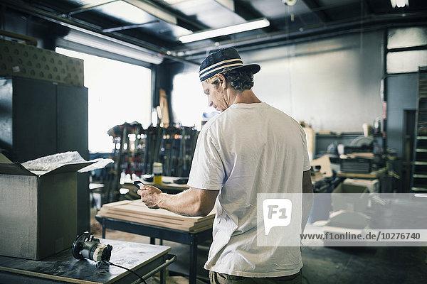 Schreiner mit Handy in der Werkstatt