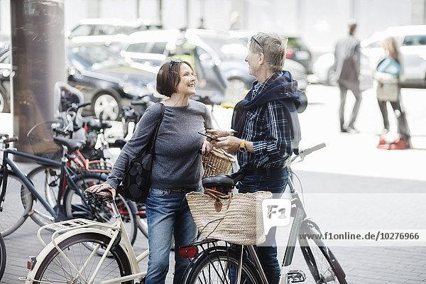 Glückliches Seniorenpaar mit Fahrrädern auf der Stadtstraße