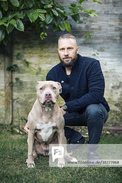 Porträt eines Mannes in der Hocke von American Pit Bull Terrier auf dem Hof