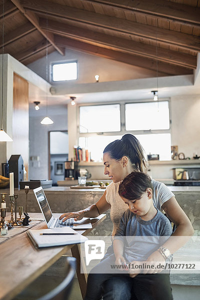 Son sitting with mother working on laptop at dining table