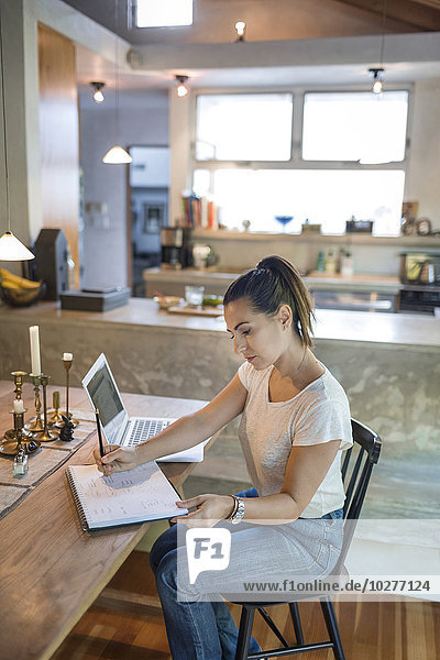 Woman working on laptop at dining table