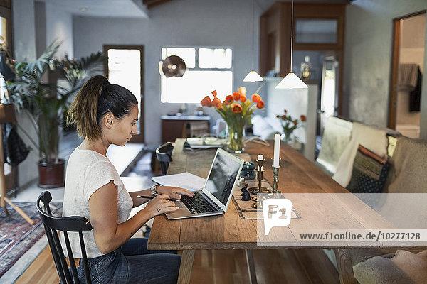 Seitenansicht der Frau bei der Arbeit am Laptop am Esstisch
