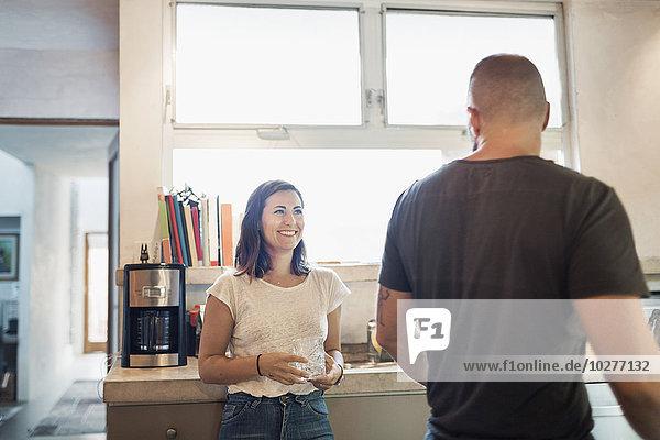 Glückliche Frau schaut den Mann in der Küche an