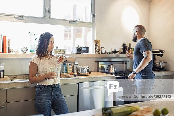 Frau überprüft die Zeit  während der Mann durch das Fenster in der Küche schaut.