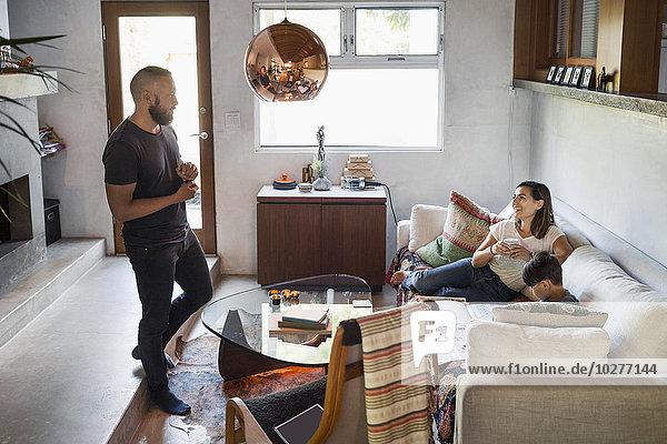 Eltern sprechen  während der Sohn zu Hause auf dem Sofa lernt.