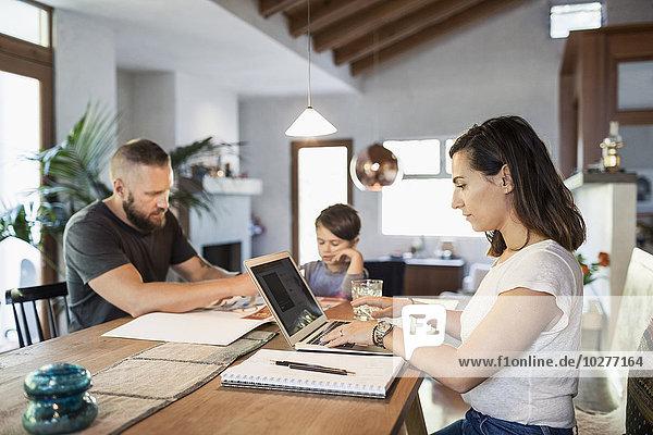 Frau arbeitet am Laptop am Esstisch mit Familie im Hintergrund