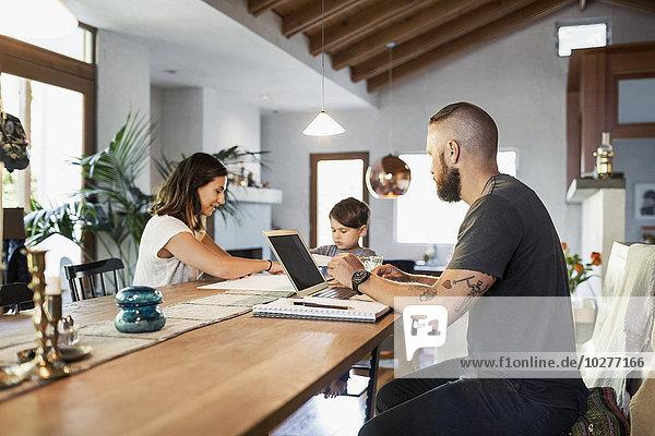 Mann  der die Familie betrachtet  während er am Esstisch im Haus arbeitet.