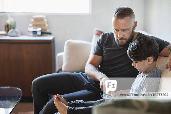 Vater hilft dem Sohn bei der Verwendung des digitalen Tabletts auf dem Sofa zu Hause.