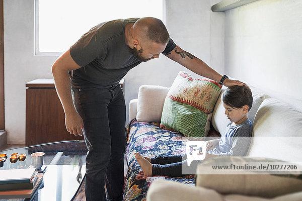 Vater streichelt Sohn mit digitalem Tablett auf dem Sofa zu Hause