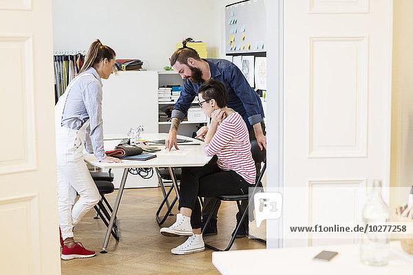 Geschäftsleute diskutieren am Schreibtisch im Kreativbüro
