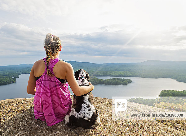 sitzend junge Frau junge Frauen sehen Steilküste Hund See Ansicht