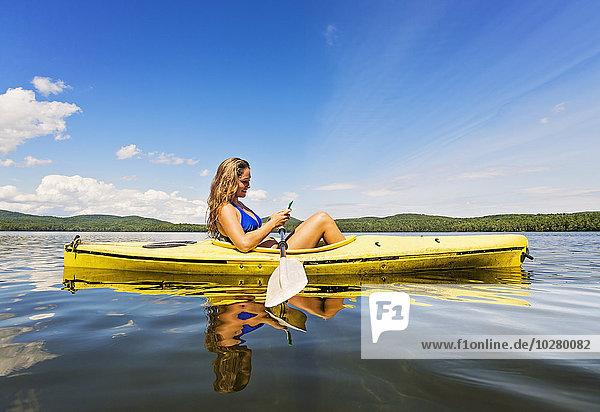 junge Frau junge Frauen benutzen See Kajak Smartphone