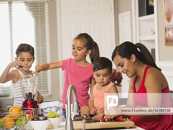 Mother and children (2-3  6-7  8-9) preparing fruit cocktails