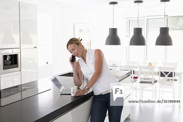 Frau sprechen Notebook Küche telefoniert