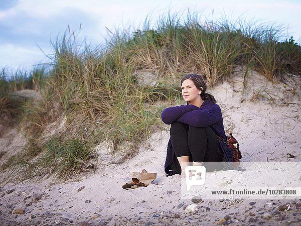 Woman sitting on sand dune